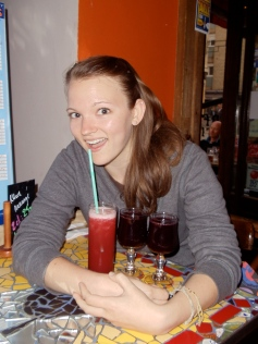 Elle posing with a strawberry margarita and two glasses of sangria.